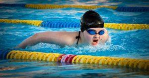 Pessoa nadando borboleta usando touca e óculos de natação - Entenda como a odontologia esportiva beneficia os atletas