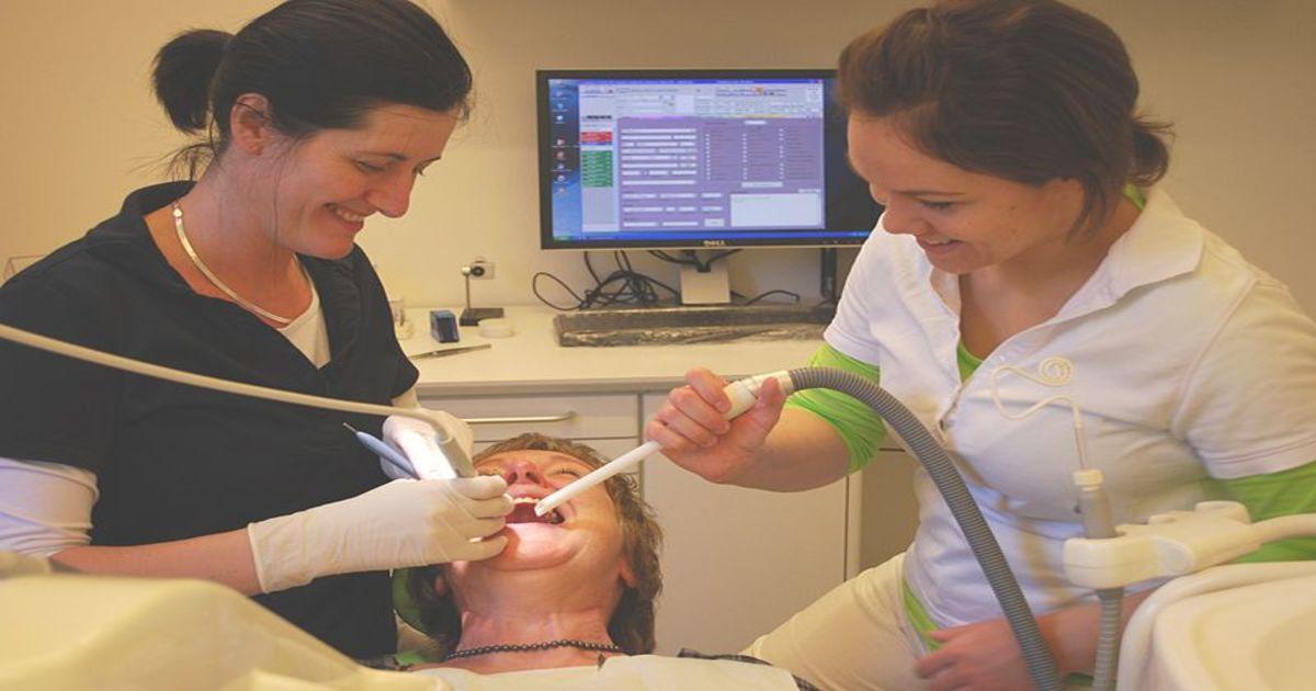 Dentista e sua assistente tratando a boca de uma paciente - Entenda as causas da pulpite, seus sintomas e tratamentos