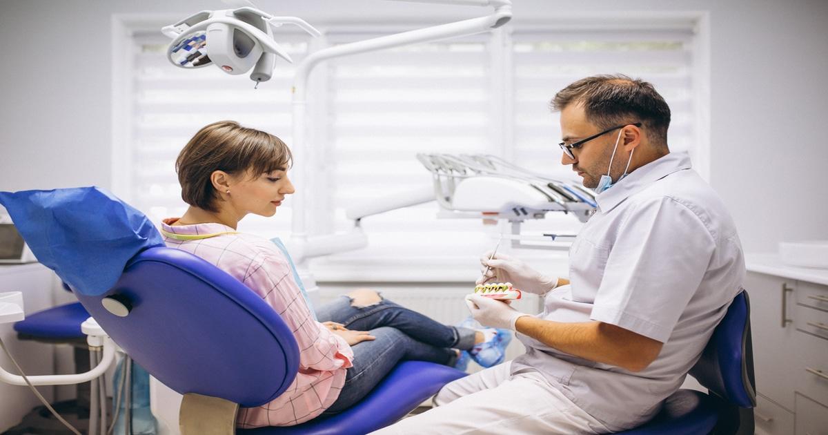 Dentista mostrando uma moldagem odontológica para uma paciente - Conheça tudo o que você precisa saber sobre arcada dentária