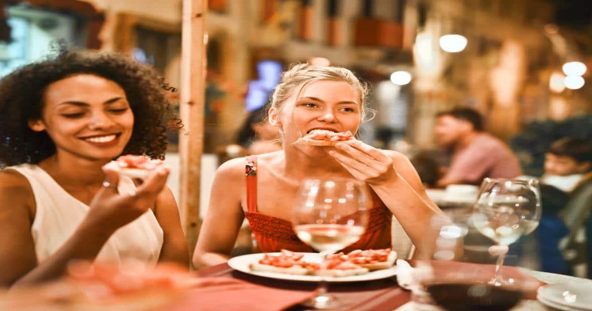 Duas mulheres comendo pizza enquanto sorriem - Conheça tudo o que você precisa saber sobre arcada dentária