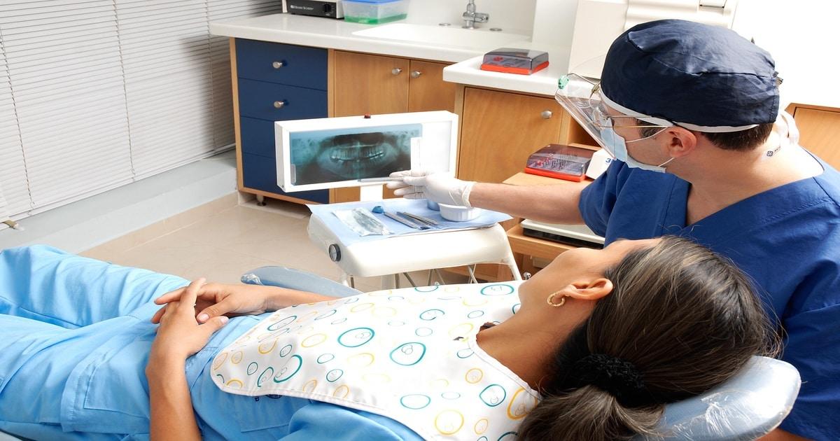 Dentista mostrando uma radiografia bucal para uma paciente - Conheça a abfração e os outros tipos de desgaste dentário