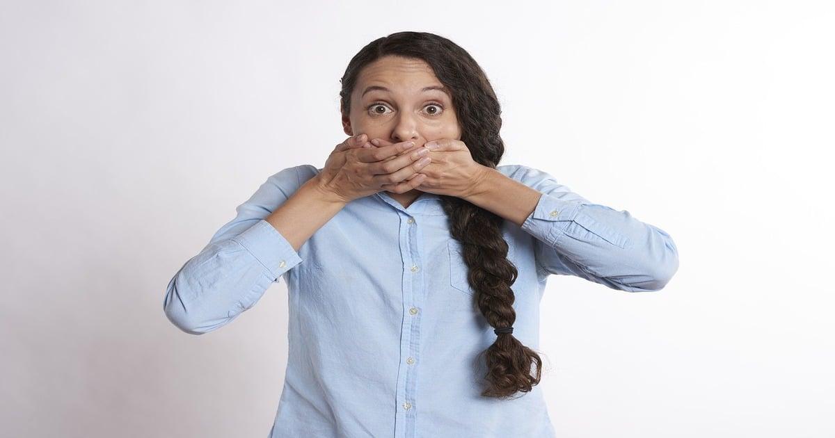 Mulher com as mãos no queixo fazendo cara de assustada - Entenda o que dente mole em adultos pode significar