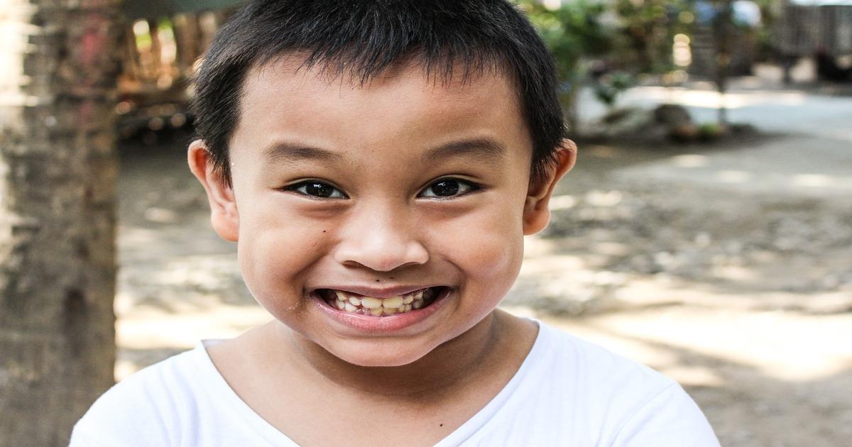 Menino sorrindo - Entenda o que dente mole em adultos pode significar