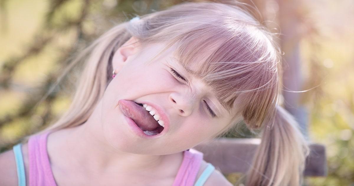 Criança fazendo careta e com a língua de fora - Conheça a candidíase oral e como funciona o tratamento