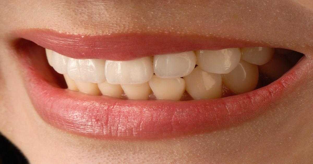 Boca com um pequeno sorriso mostrando os dentes - Conheça a cerâmica feldspática em procedimentos estéticos