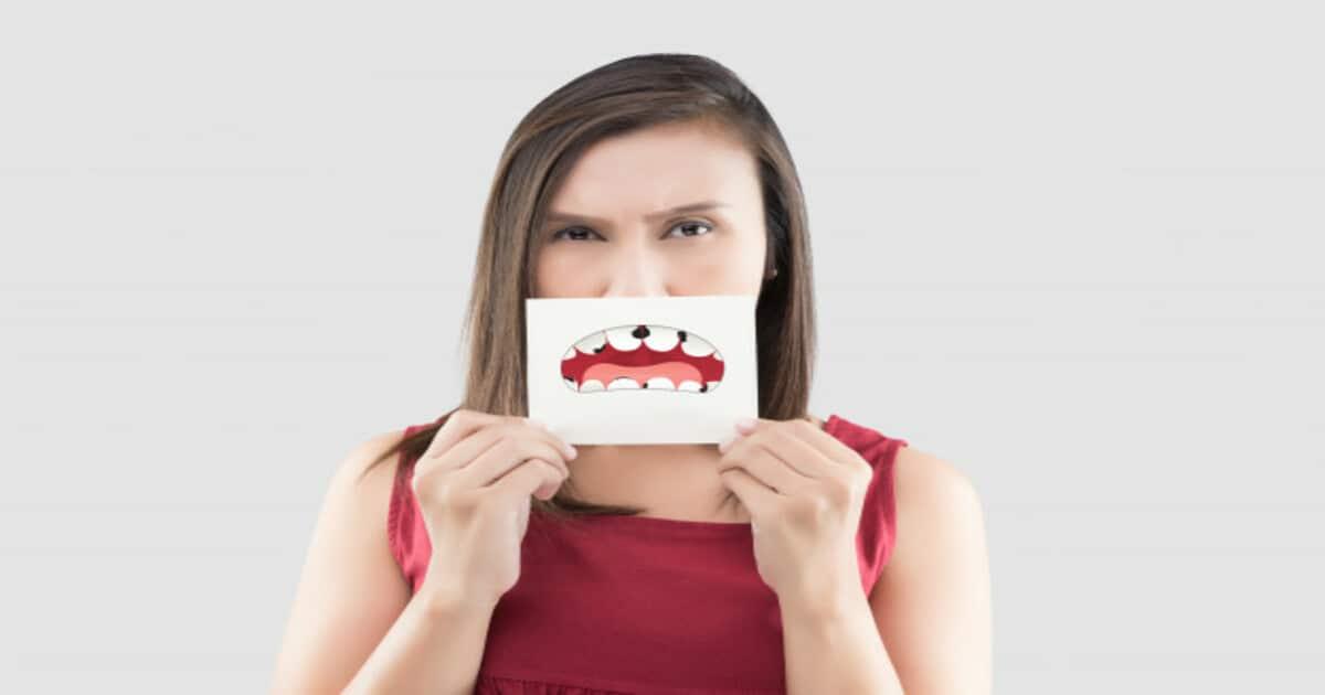 Mulher segurando uma ilustração de um dente cariado em frente sua boca - Conheça o trismo, responsável por travar a mandíbula do paciente
