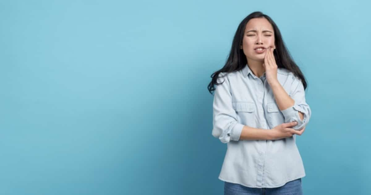 Mulher com a mão na mandíbula fazendo cara de dor - Conheça o trismo, responsável por travar a mandíbula do paciente