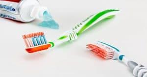 Duas escovas de dentes coloridas e uma pasta de dente ao lado com o creme dental saindo - Conheça tudo o que precisa saber sobre a Bitufo