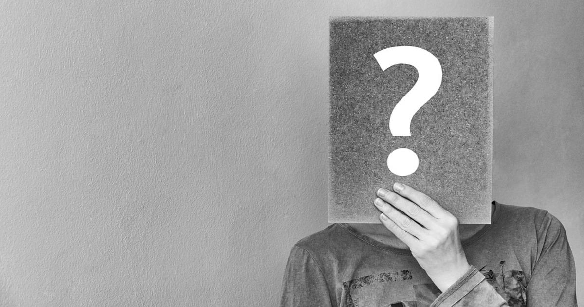 Pessoa segurando uma placa com uma interrogação tapando seu rosto - Veja tudo o que você precisa saber sobre a Endodontia