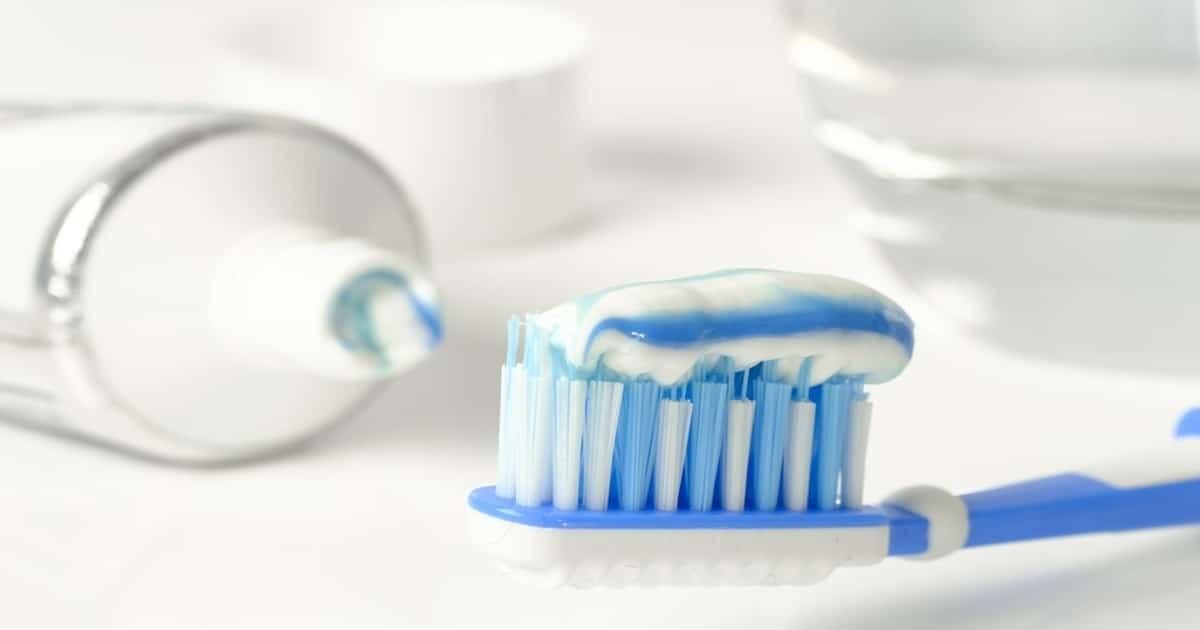Escova de dentes com pasta e um creme dental ao lado - Veja tudo o que você precisa saber sobre a Endodontia