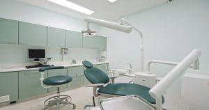 Sala de atendimento de um consultório com uma cadeira odontológica ao centro, uma cadeira ao lado e uma bancada de dentista ao fundo- Saiba como montar seu consultório com a franquia Sorridents