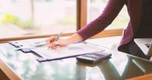 Pessoa escrevendo numa prancheta, ao seu lado, na mesa, tem uma calculadora - Conheça a tabela VRPO, que ajuda a precificar procedimentos