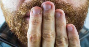 Homem com barba com a mão na frente da boca - Entenda o que é eructação e o que pode causar