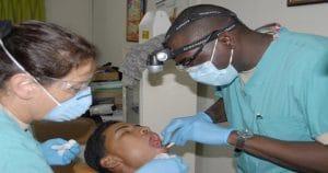 Dentista e assistente examinando a boca do paciente - Você conhece o SINOG e sabe qual é sua importância?