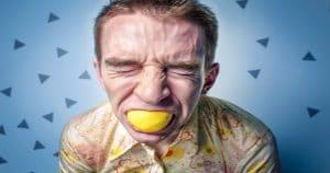 Gosto ruim na boca pode vir acompanhado do mau hálito matinal ou significar condições mais graves Uma das melhores sensações da vida é poder sentir o gosto daquela comida ou bebida que você ama, não é? Contudo, além de nos ajudar a apreciar os sabores que gostamos, as papilas gustativas também podem intensificar um sabor que não gostamos e deixar um gosto ruim na boca. O pior nessa situação é que, às vezes, aquele constantegosto ruim na bocanão tem a ver com o que você comeu ou deixou de comer, mas insiste em permanecer ali. O que pode ser isso? O constante gosto ruim na boca pode possuir diversas causas. Ele pode ser resultado da baixa produção salivar, proliferação de bactérias no ambiente oral, sintoma de alguma doença ou até mesmo vir acompanhado do famoso mau hálito no início do dia. Uma coisa é certa: se o gosto ruim na boca não passar após uma boa higienização bucal, sua causa deve ser investigada! Como saber se o gosto ruim que sinto na boca é normal? Para saber se o estranho gosto que você sente na boca é considerado normal, você deve notar quando ele ocorre. É logo ao acordar de algumas horas de sono? Seria, então, ao comer algum alimento com gosto mais forte, ácido ou amargo? Ou ele costuma aparecer após o uso do tabaco? Se o gosto ruim aparece em algum dos casos acima, ele pode ser considerado normal e decorrente justamente dessas ações. Por exemplo, o gosto ruim aliado ao mau hálito matinal é considerado normal pelos dentistas. Isso porque, quando dormimos, ficamos um longo período com a boca fechada, o que diminui a produção de saliva no ambiente oral. Quando isso ocorre, o pH da boca torna-se mais ácido, o que favorece a proliferação de bactérias dentro da boca, já que elas sobrevivem mais facilmente em ambientes mais ácidos. Assim, a baixa concentração de saliva, aliada a ação desses microrganismos, resultam no gosto ruim e no mau hálito matinal, conhecido como halitose. Nos outros dois casos, o gosto ruim na boca pode ser mais compreensível, já que 