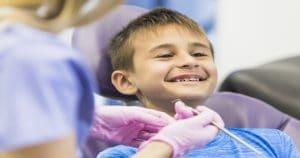Criança sorrindo sentada na cadeira do dentista.
