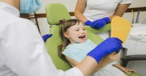 Criança mostrando os dentes enquanto se olha no espelho, segurado pelo dentista.