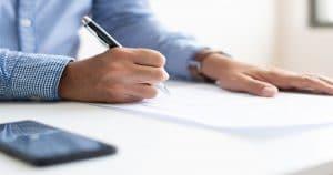 Homem escrevendo numa folha em branco - Entenda tudo o que você precisa saber sobre o CNES