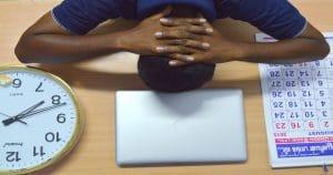 Pessoa com as duas mãos na nuca e com a cabeça abaixada. Embaixo dela há um relógio, um notebook e uma agenda.