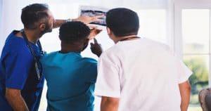 Três dentistas olhando e comentando uma radiografia bucal, que poderia ser evitada com o check up preventivo digital. Os dois da esquerda usam roupas cirúrgicas azuis, enquanto o da direita usa roupa branca.