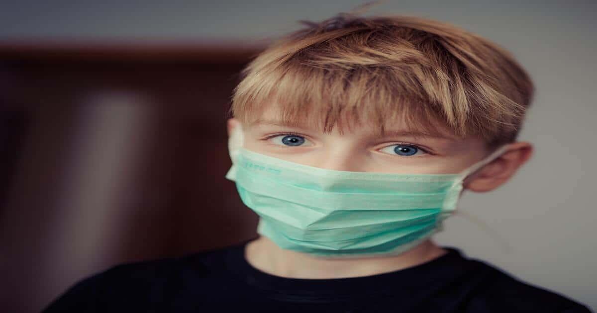 Criança com máscara cirúrgica no rosto.