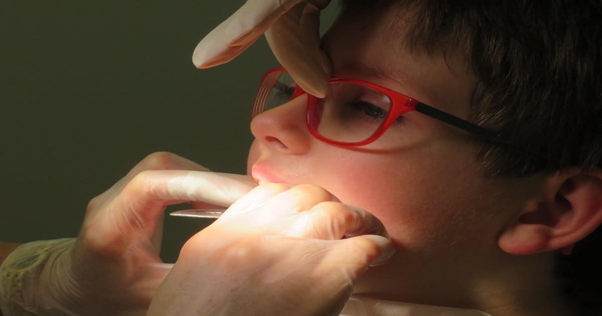 Dentista com as mãos na cavidade bucal de uma criança que usa óculos vermelhos