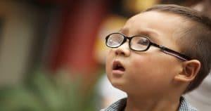 Criança usando óculos olhando para o lado - Entenda tudo sobre a a Síndrome de Stickler