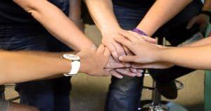 Imagem com cinco mãos unidas