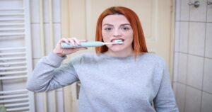 Mulher de blusa cinza em frente ao espelho escovando os dentes com uma escova de dentes elétrica azul.