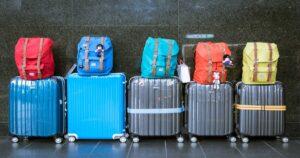 Cinco malas enfileiradas uma do lado da outra com mochilas em cima.