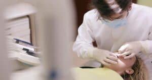 Dentista, usando máscara, óculos, roupa branca e luvas, examina a cavidade bucal de uma paciente, sentada na cadeira odontológica.