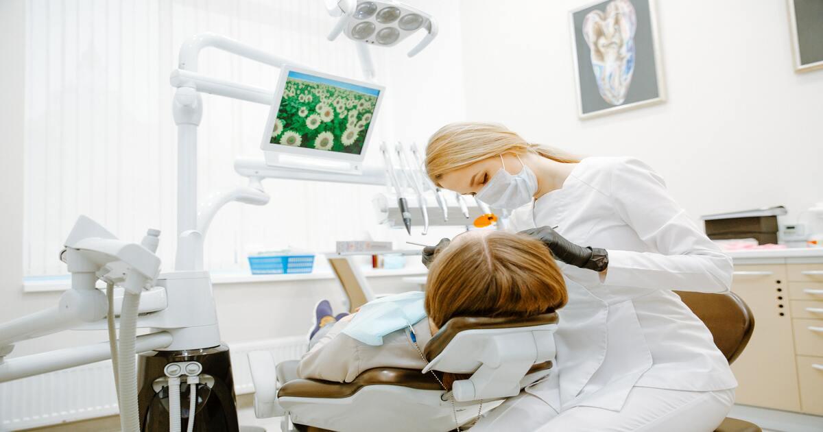 Dentista examinando a boca de sua paciente, que está deitada na cadeira odontológica.