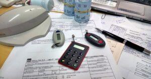 Uma mesa com boletos bancários e, sobre eles, três tokens de banco, uma caneta e três rolos de papel de máquina de cartão de crédito.