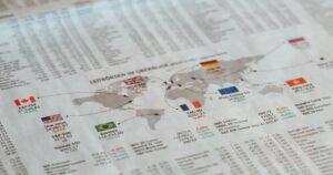 Jornal estampando o mapa mundi e as economias de alguns países.
