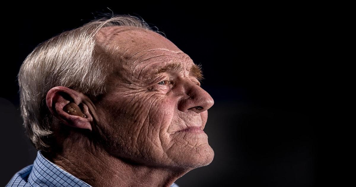 Homem idoso olhando para o lado com tom de seriedade.
