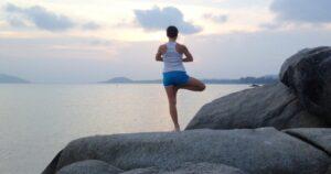 Pessoa se equilibrando em uma perna só em cima de uma pedra. Ao fundo, uma paisagem de entardecer.