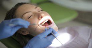 Paciente tendo sua boca examinada pelo dentista, que usa luvas azuis e segura instrumentos odontológicos.