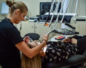 Paciente sentada na cadeira odontológica sendo atendida pela dentista. Ambas usam roupas pretas.