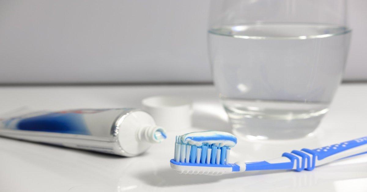 Em cima de uma pia branca, há uma escova azul e branca com pasta sobre suas cerdas, uma pasta de dente azul e prateada e um copo de água.
