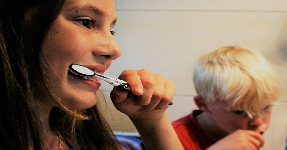 Duas crianças escovando os dentes, uma menina, que usa uma escova preta e branca, e um menino, que está de camiseta vermelha.