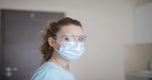 Profissional da saúde usando óculos de proteção e máscara olhando para o lado.