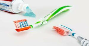 Mesa branca com uma pasta de dente à esquerda da imagem e duas escovas de dente postadas ao seu lado.